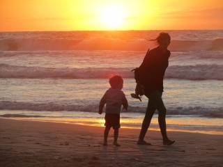 Mother and child walking on a beach at sunset